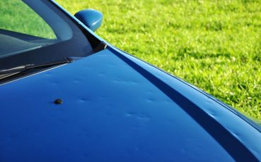34782111 - hail damage on the hood of a blue car